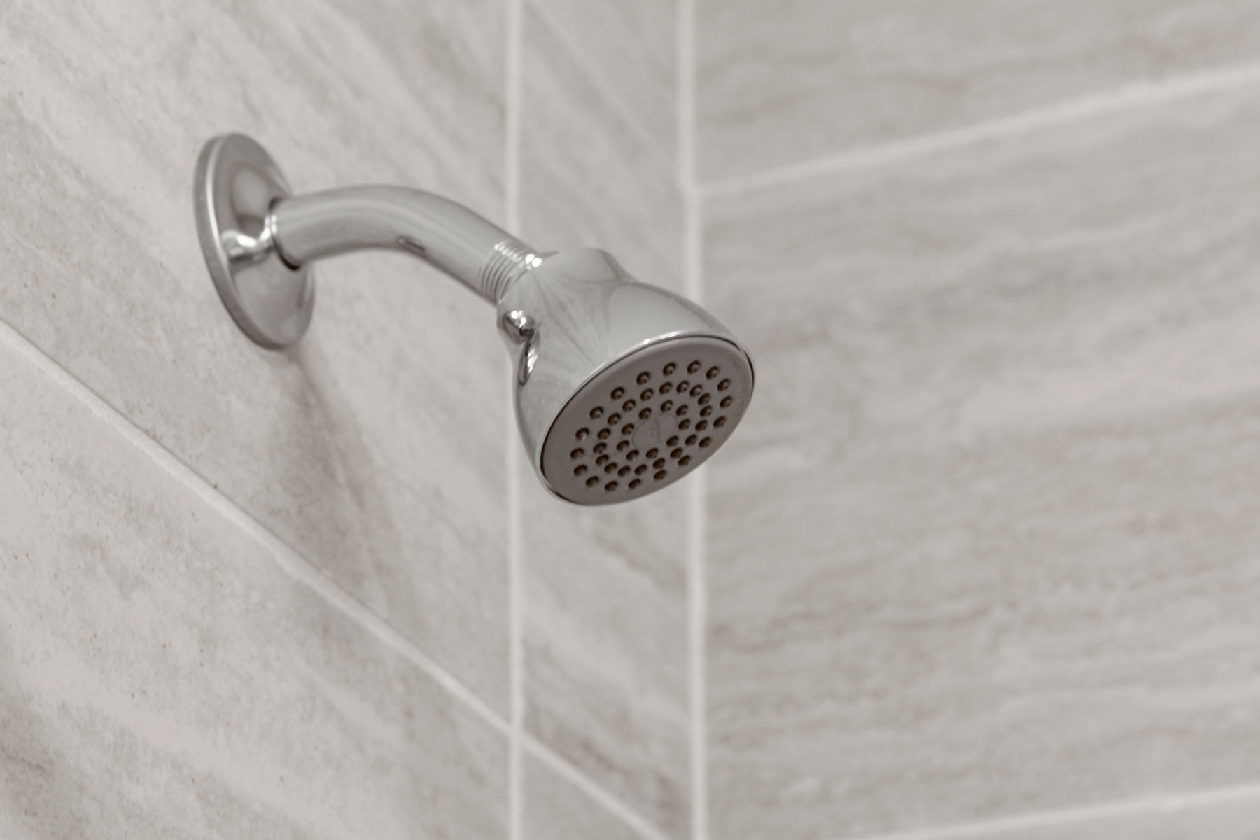 Detail of chrome showerhead and tiles