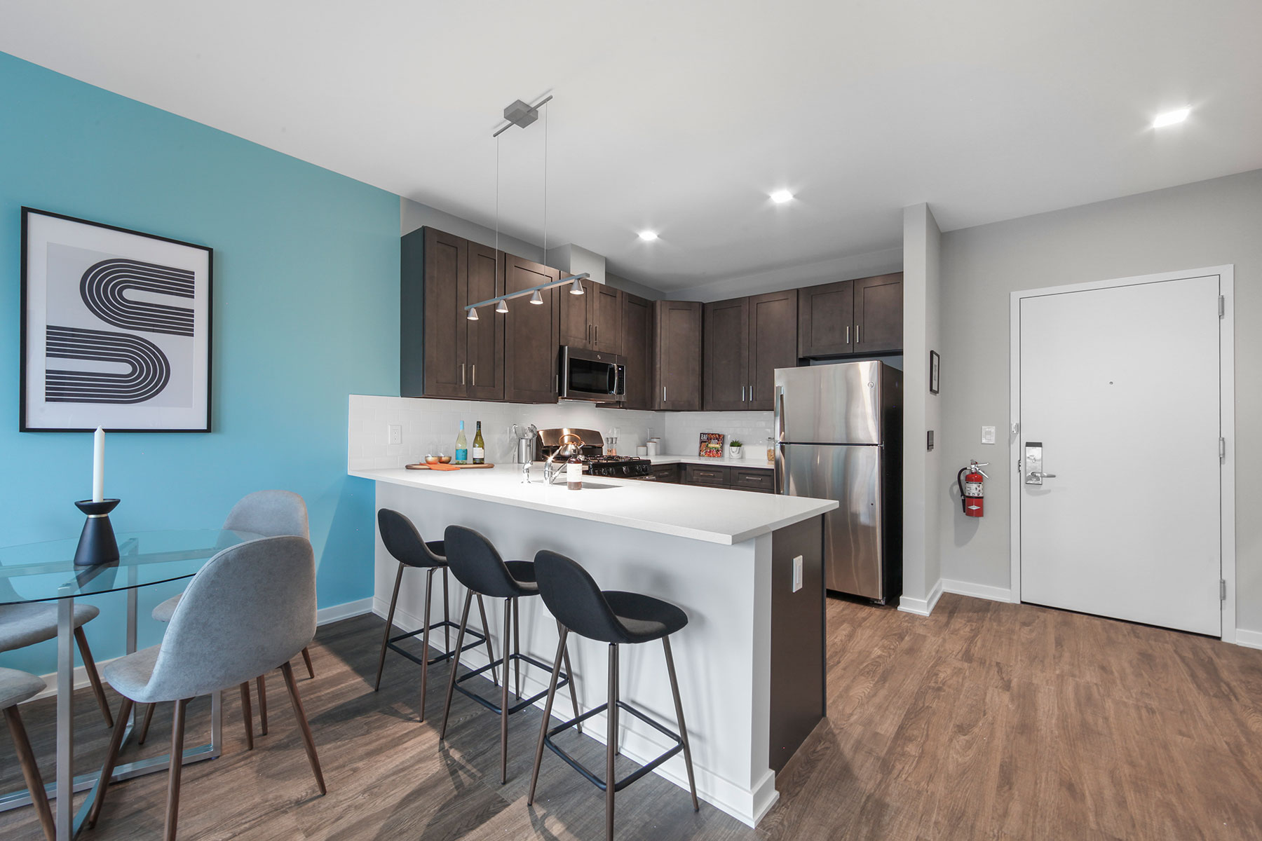 Bright modern kitchen and dine in seating near entrance, with barstools at counter, dark wood cabinetry, stainless steel appliances and modern fixtures and wood floors